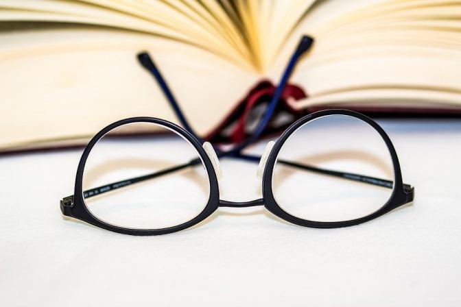 Vor einem Buch liegt eine Brille
