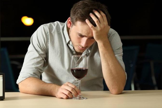 Mann mit Weinglas schaut depressiv aus