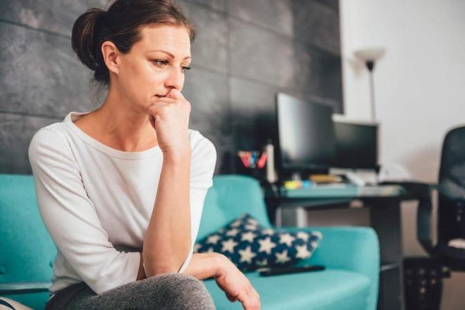 Frau, eventuell mit Burnout, sitzt grübelnd auf dem Sofa