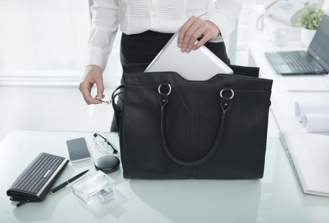 Eine Business Frau gibt einen Laptop in eine Handtasche
