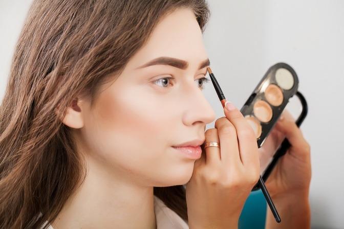 Das Gesicht einer Frau wird mit Camouflage Make-up geschminkt