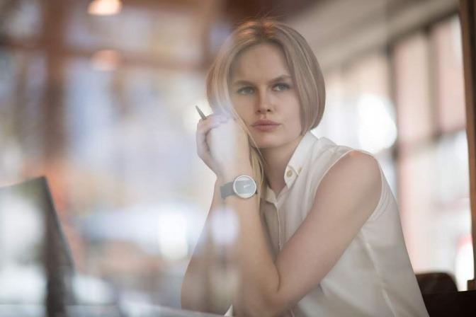 Eine Frau sitzt an einem Tisch und grübelt nachdenklich über ein Problem.
