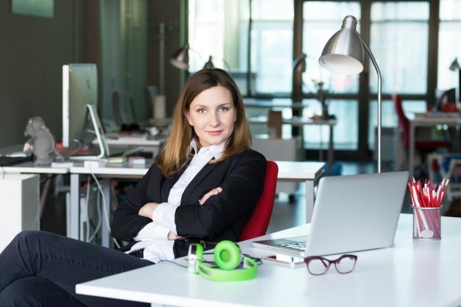 Frau in Businessoutfit sitzt im Cafe und blickt fordernd und selbstbewusst in die Kamera.
