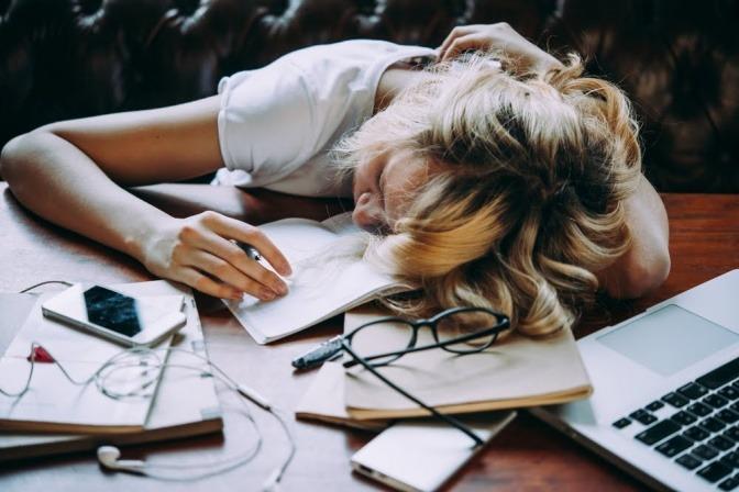 Frau liegt erschöpft an ihrem Schreibtisch