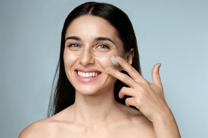 Eine Frau trägt sich Tagescreme für den Make-up Trend Cloud Skin auf