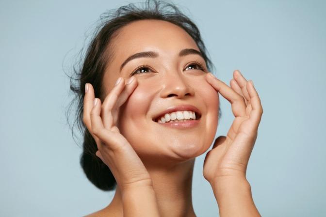 Eine Frau mit Make-up Cloud Skin lächelt