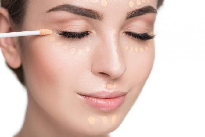 Eine Frau hat Concealer-Punkte in ihrem Gesicht