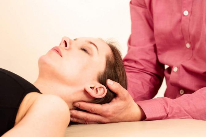 Therapeut hält die Hände im Nacken einer Patientin