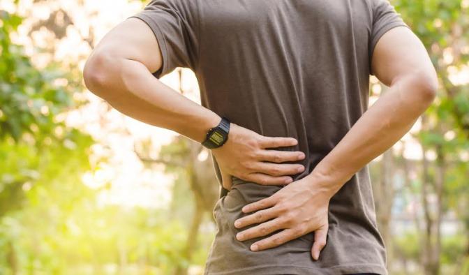 Mann hält sich den schmerzenden Rücken