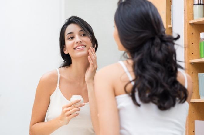 Eine Frau gibt Creme gegen Falten durch trockene Haut in ihr Gesicht