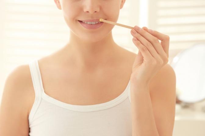 Waxing an der Oberlippe, um Damenbart zu entfernen