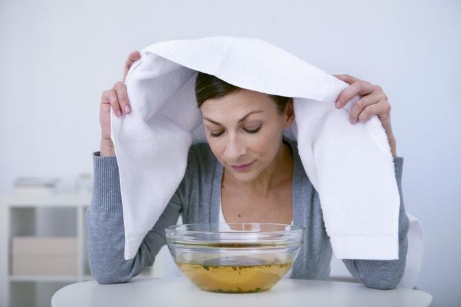 Eine Frau macht ein Dampfbad gegen Pickel
