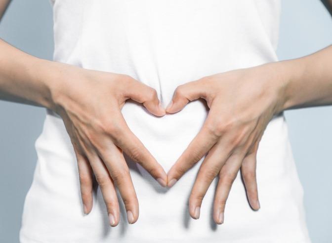 Frau formt mit Händen Herz über ihrem Bauch