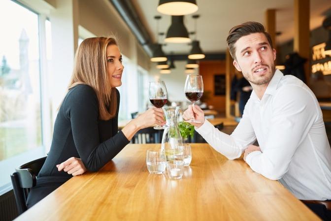 Junges Paar trinkt Wein bei einem Rendezvous im Restaurant oder Bistro.
