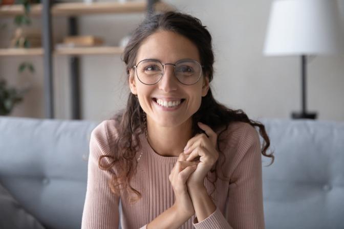 Eine Frau lacht mit übertriebener Freundlichkeit