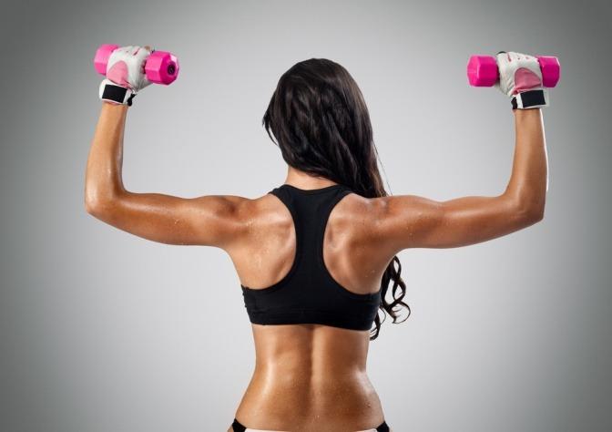 Frau von hinten mit Hanteln beim Sport