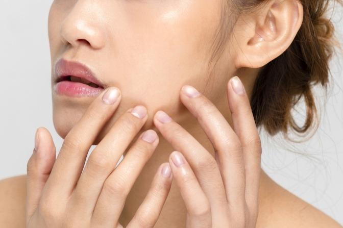Junge Frau untersucht Gesichtshaut