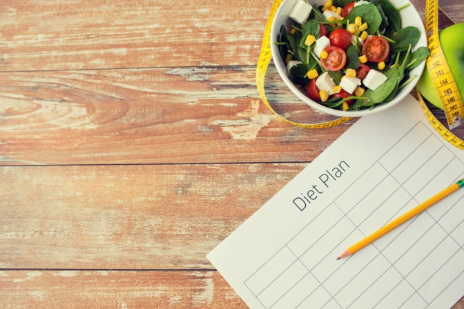 """Auf einem hölzernen Untergrund liegen ein Zettel mit Stift und eine kleine Schüssel Salat. Auf dem Zettel steht geschrieben: """"Diätplan""""."""