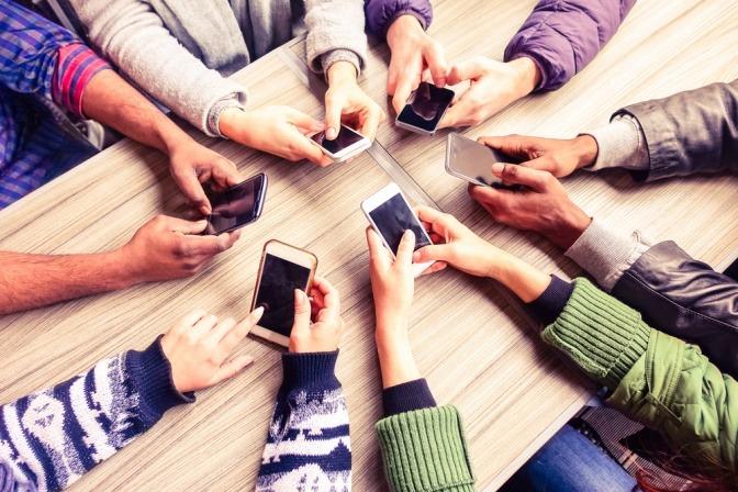 Mehrere Menschen haben ein Handy in der Hand und bilden einen Handkreis