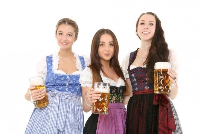 Drei Frauen stehen nebeneinander im Dirndl und halten jeweils einen großen Bierkrug in der Hand