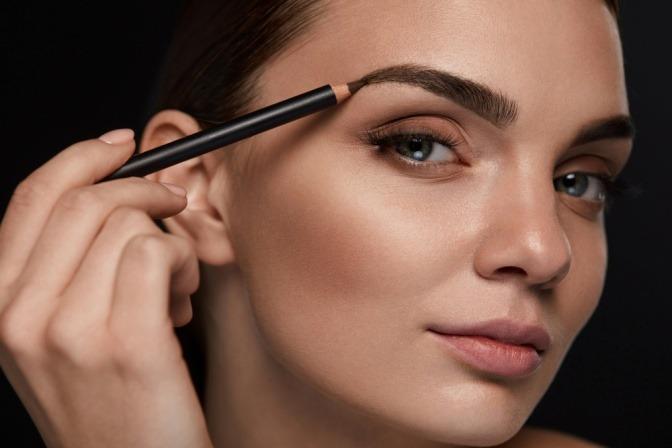 Eine Frau schminkt die dünnen Augenbrauen