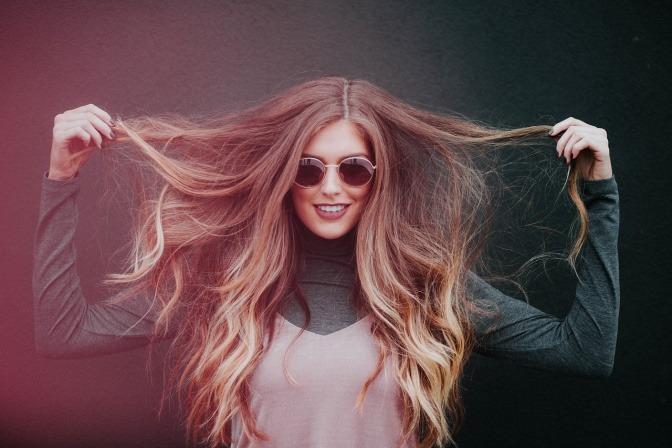 Eine Frau hält ihre dünnen Haare beiseite, vielleicht auch Haarausfall