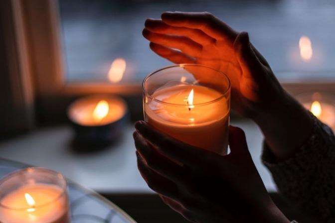 Eine Hand über einer Duftkerze, die warme Atmosphaere verbreitet