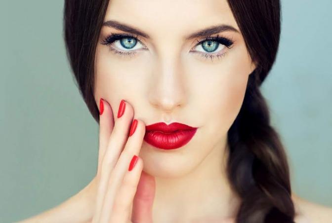Eine Frau mit dunklen Haaren und heller Haut trägt roten Lippenstift