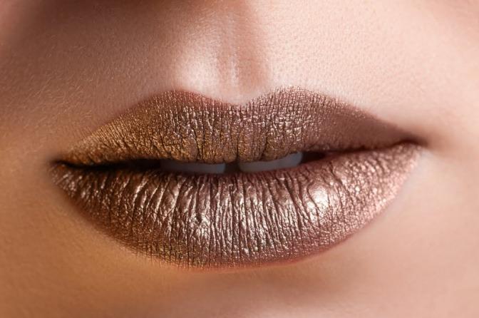 Eine Frau hat dunkle Haut und goldenen Lippenstift