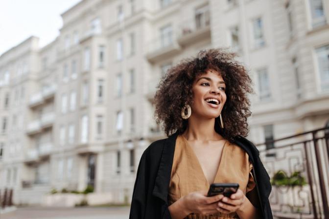 Eine junge Frau lächelt und hält ihr Handy in der Hand