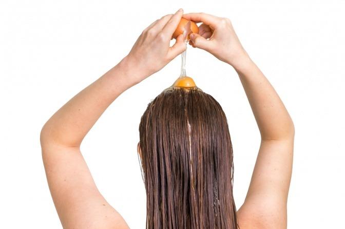 Eine Frau gibt Eier auf ihre Haare