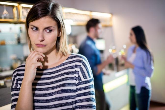 Frau blickt bei einer Hausparty eifersüchtig auf ein Pärchen hinter ihr.