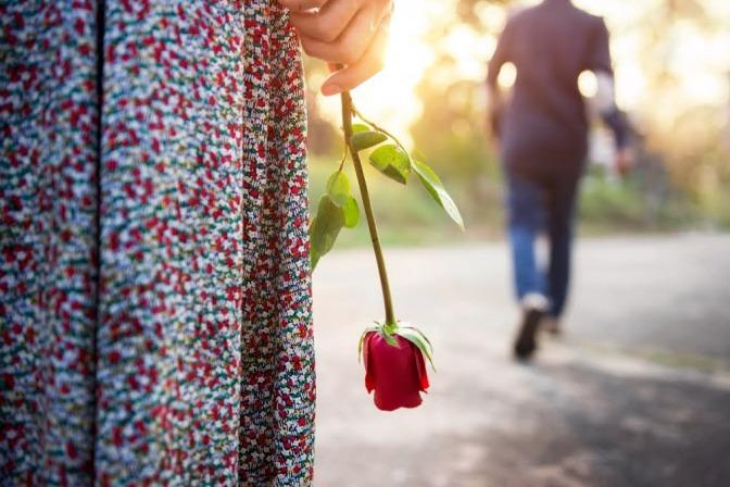 Eine Frau hält eine Rose in einem am Körper anliegenden Arm, während Ihr vermeintlicher Partner gerade von ihr weg geht.