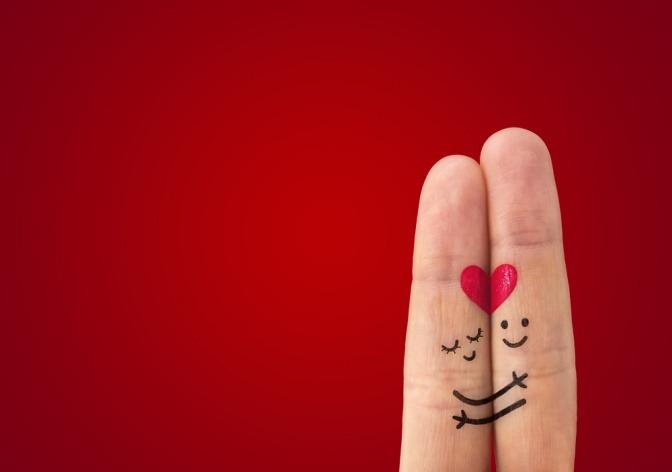 Wir sehen zwei Finger einer Hand, Zeige- und Mittelfinger, die ganz eng aneinander liegen. Ein romantisches Smiley ist mit roter Farbe auf die Fingerkuppen gemalt.
