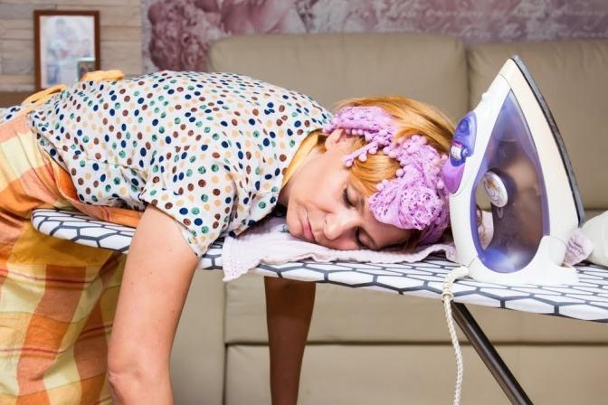 Eine Hausfrau ist beim Bügeln weggenickt und liegt schlafend mit dem Oberkörper auf einem stehenden Bügelbrett.