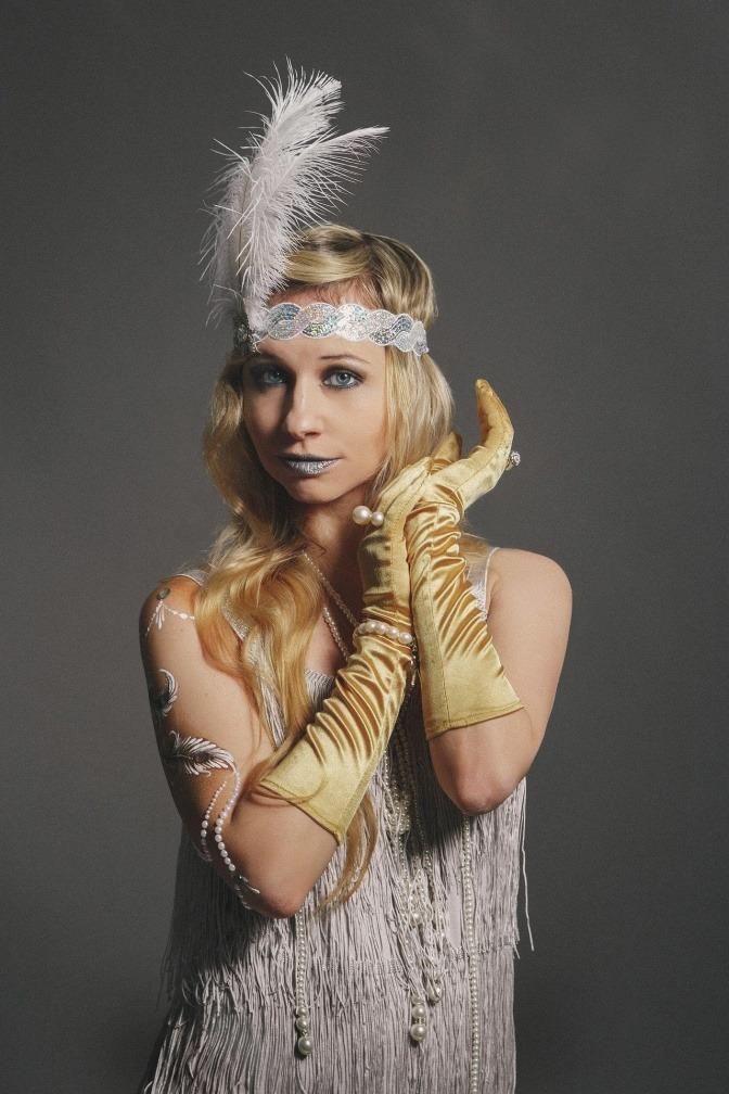 Frau mit eleganter Frisur und Feder im Stirnband