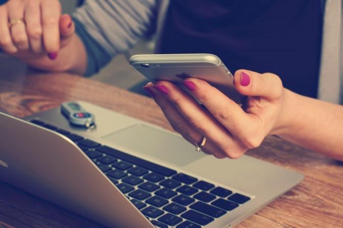 Eine Frau macht sich über Elektrosmog Auswirkungen wohl keine Sorgen, da sie mehrere elektronische Geräte um sich herum platziert hat.