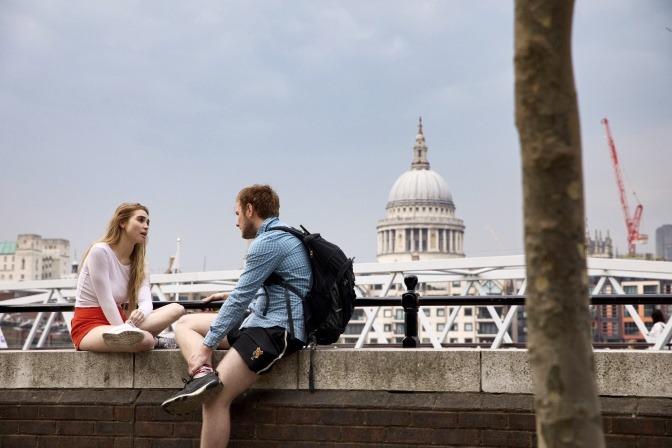 Ein Mann und eine Frau sitzen auf einer Brüstung und unterhalten sich.