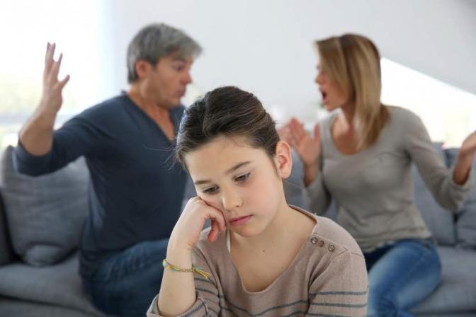 Eltern streiten im Hintergrund, ihre kleine Tochter sitzt apathisch im Vordergrund und blickt ins Leere.
