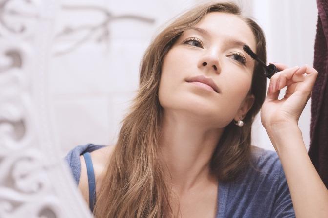 Frau steht vor dem Spiegel und schminkt sich