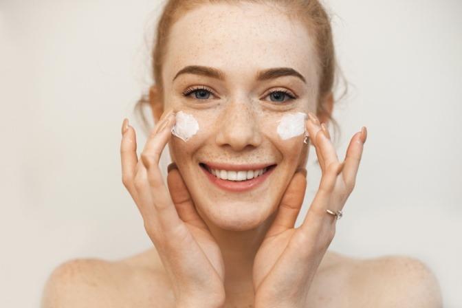 Frau mit empfindlicher Haut cremt ihr Gesicht ein