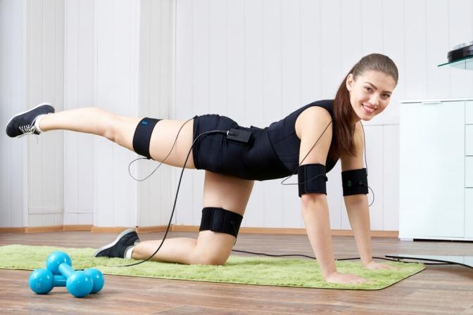 Eine Frau macht Übungen am Boden mit einem EMS-Gerät