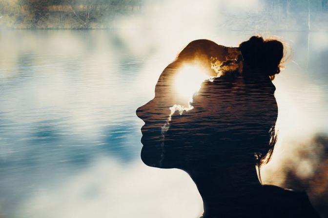 Die seitliche Schattensilhoeutte einer Frau, die an einem See sitzt. Ihr Körper ist transparent. Es wirkt, als sei die Energie ihres Körpers mit der spirituellen Energie der Umgebung verknüpft.