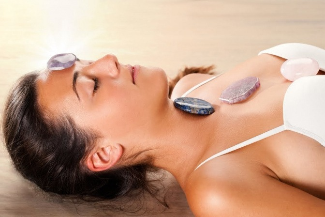 Eine Frau unterzieht sich einer energetischen Behandlung. Sie liegt rücklings auf einer Liege, während auf ihrem Oberkörper und ihrem Kopf kleine Steine an die Stellen gelegt wurden, an der die Hauptchakren sitzen.