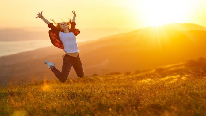 Frau macht einen Luftsprung im Sonnenuntergang