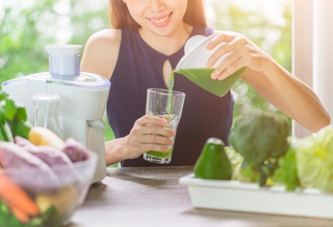 Eine Frau trinkt Gemüsesaft zum Entschlacken bei Neumond