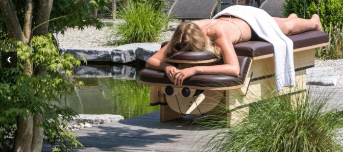 Frau liegt entspannt auf einem Massagestuhl