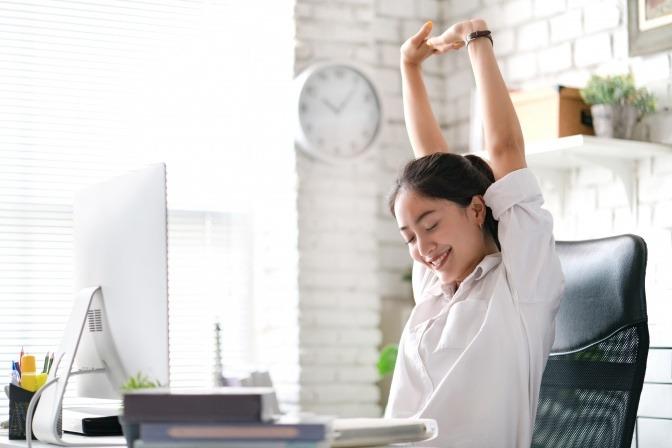 Glückliche Frau streckt sich auf ihrem Bürostuhl.