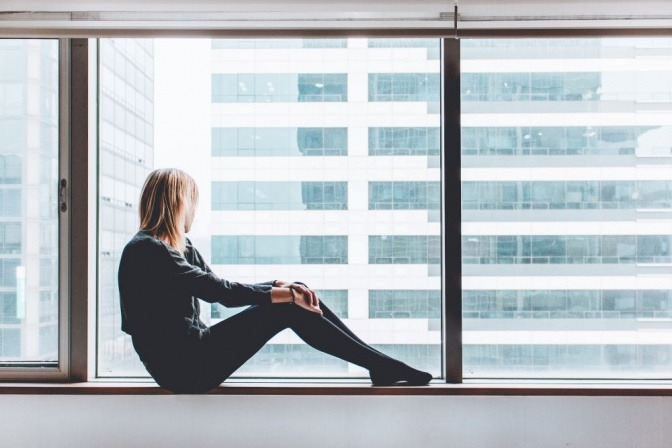 Eine Frau mit guten Knochen sitzt entspannt am Fenster