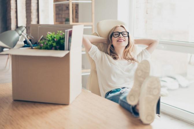 Eine Frau legt entspannt nach einem Neubeginn die Füße auf den Tisch